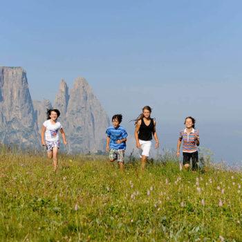 Kinder laufen über Almwiese